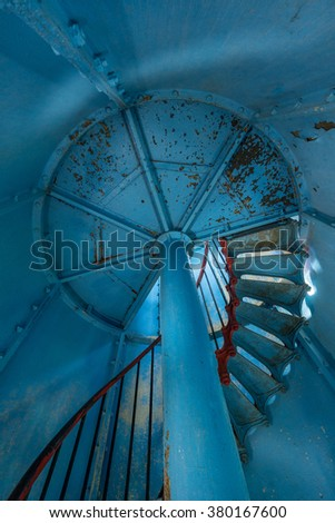 Old lighthouse on the inside. Red iron spiral stairs, round window and blue wall. Kihnu, small island in Estonia. Europe - stock photo