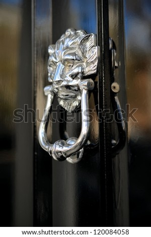 Old lion's head door knob on a black door in a London mansion - stock photo