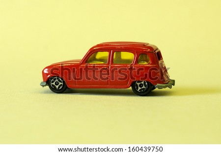 old little red toy car on a yellow background - stock photo