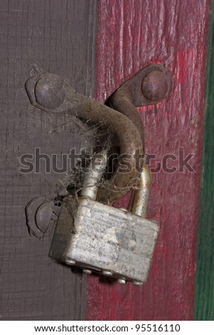 old lock and cobwebs on a rusty latch on an old painted building. - stock photo