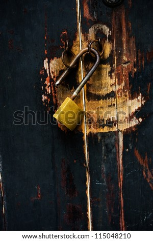 Old lock key on the black wood gates