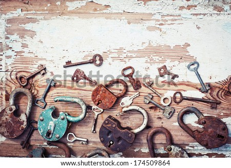 Old locks and keys on wooden plank - stock photo