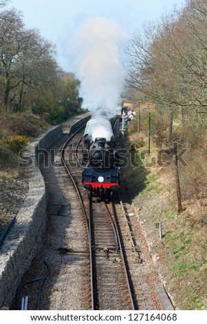 old locomotive leaving the railway station - stock photo