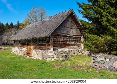 Old log barn with a thatched roof. Hiiumaa open-air museum Mihkli farm, Estonia. Most of the buildings date to the middle of the 18th century. One of the best preserved farmsteads. - stock photo