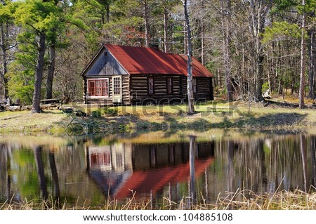 Old Log Cabin reflection in a pond. Michigan forest USA - stock photo