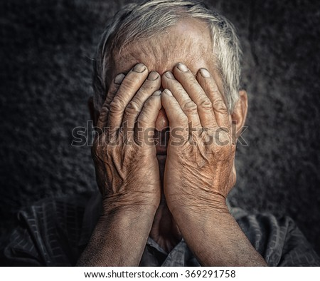 Old & lonely. Closeup portrait sad depressed stressed gloomy senior old man worried covering face isolated black gray wall background. Negative human emotions face expression feeling reaction attitude - stock photo