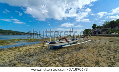 Old lonely fishing boat on the coastline of island Bali in Indonesia - stock photo