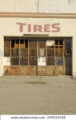 Old long closed up tire shop in a small town on an old highway in northern California - stock photo