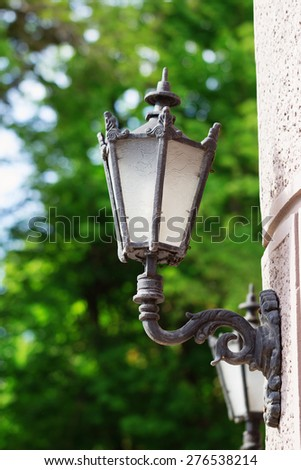 Old looking glass lantern on the wall on the street - stock photo