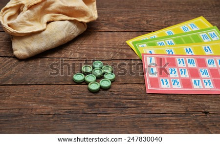 Old lotto game pieces and cards on wood background - stock photo