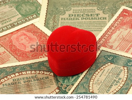 Old love: red heart shaped jewelery box on old, historical Polish notes, bills from Second World War.  - stock photo