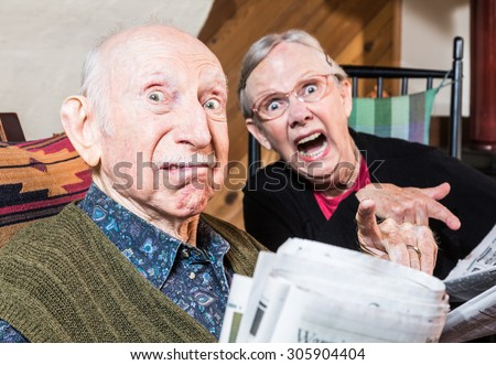 Old mad couple reading a newspaper in their living-room - stock photo