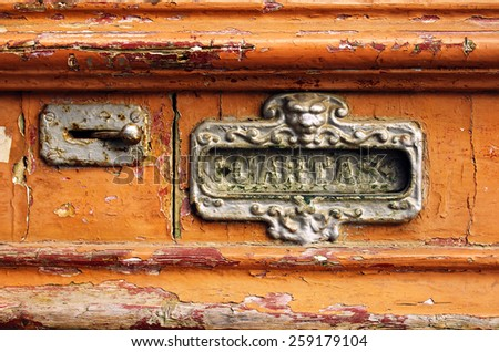 Old mailbox slot in an old wooden door painted orange - stock photo