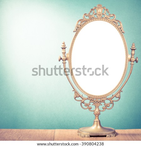 Old makeup mirror frame on table. Retro style filtered photo - stock photo