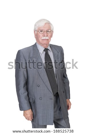 old male with spectacles in a gray suit standing looking into the camera  - stock photo