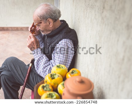 old man alone on his house terrace. concept about seniority and aging - stock photo