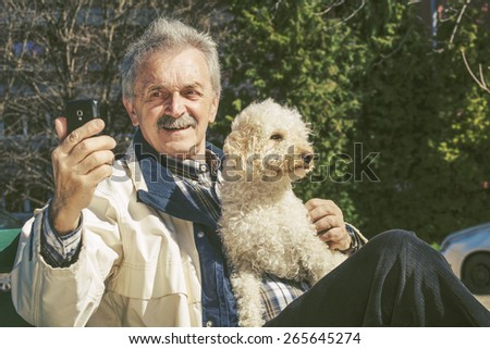Old man and a dog in the park on a bench  - stock photo