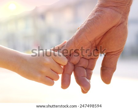 old man and a kid holding hands together on sunset  - stock photo