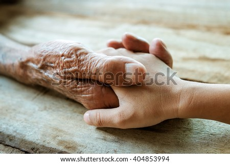 old man and a kid holding hands together on the wood table  - stock photo