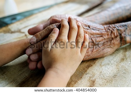 old man and a kid holding hands together on the wood table