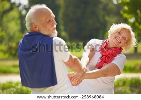 Old man and senior woman dancing together in a garden in summer - stock photo