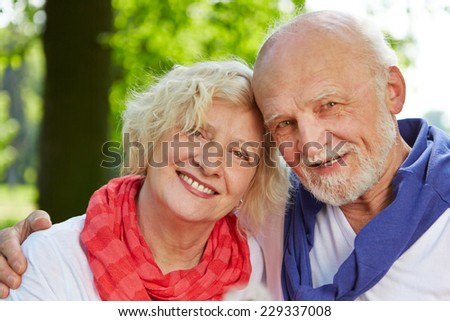 Old man and woman as senior couple in nature in fall - stock photo