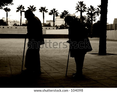 Old man and woman walking with sticks - stock photo