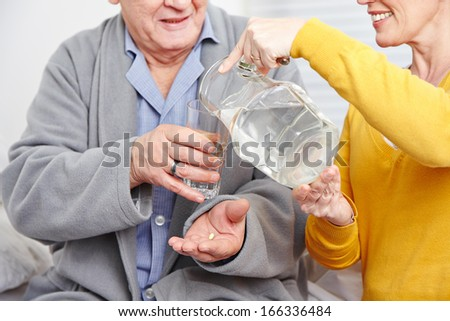 Old man at home taking a pill with glass of water - stock photo