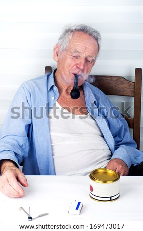 Old man bohemian enjoying smoking pipe