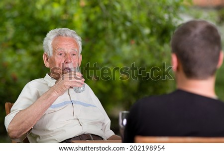 Old man drinking water in garden while sitting with grandson - stock photo