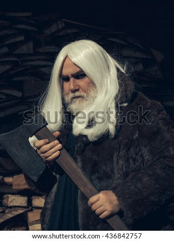 Old man druid with long silver hair and beard in fur coat stands with axe on woodpile background