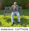 old man enjoys sitting on a bench in his garden - stock photo