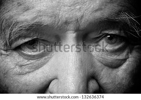 old man face part closeup eyes looks at camera monochrome image - stock photo