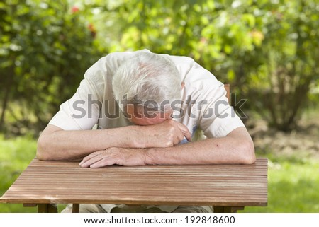 Old man fall asleep with head on table in garden - stock photo