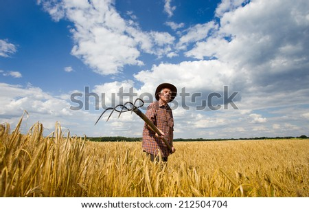 Old man farmer working with fork in barley field  - stock photo