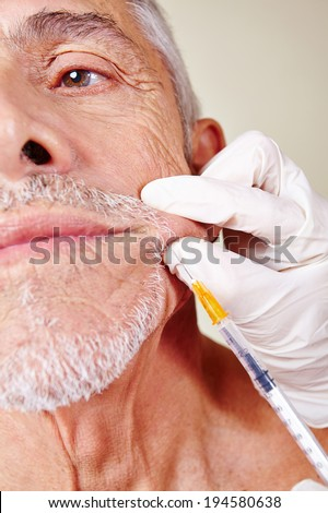 Old man getting cosmetic surgery on corner of mouth in beauty clinic - stock photo