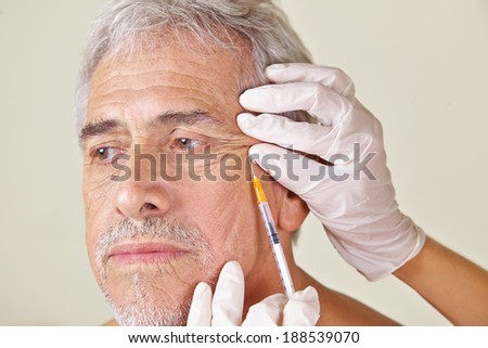Old man getting wrinkles treatment against crow's feet in beauty clinic - stock photo