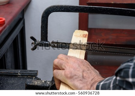 old man hand planers wood in the workshop