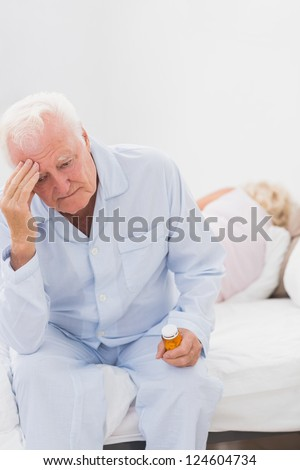 Old man having a headache while woman sleeping on the bed - stock photo