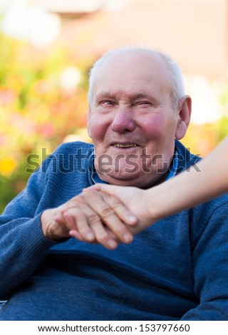 Old man holding a female hand, being happy. - stock photo