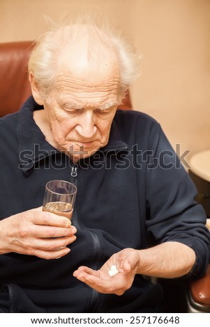 old man holding a glass of water and a mix of pills - stock photo