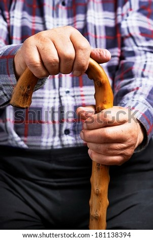 Old man holding a stick - stock photo