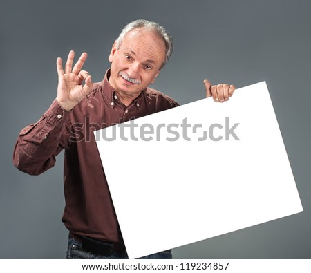 old man holding empty billboard and shows sign OK