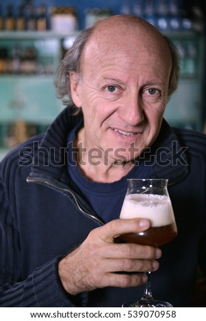 Old man holding glass of beer