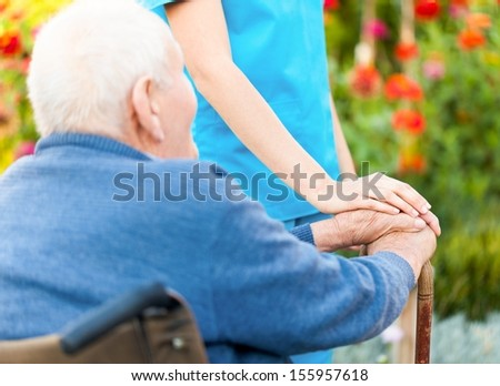 Old man holding his stick, sitting in wheelchair. - stock photo
