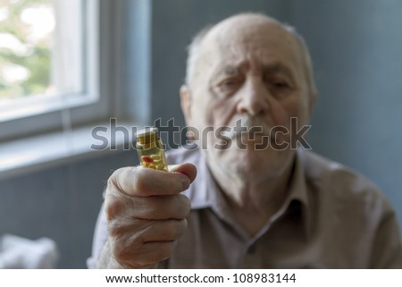 old man holding pills and he needs help - stock photo
