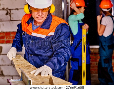 Old man in blue  builder with circular saw. - stock photo