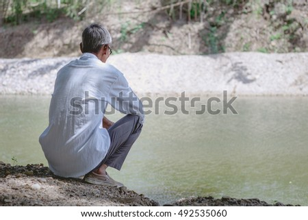old man in glasses sitting near pond