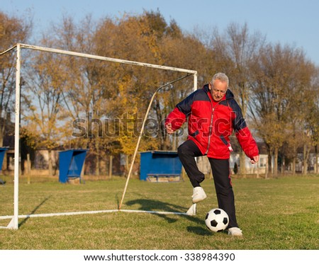Old man in seventies kicking a soccer ball on playground with goal behind him