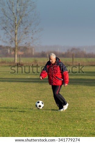 Old man in seventies kicking a soccer ball on the grass field - stock photo